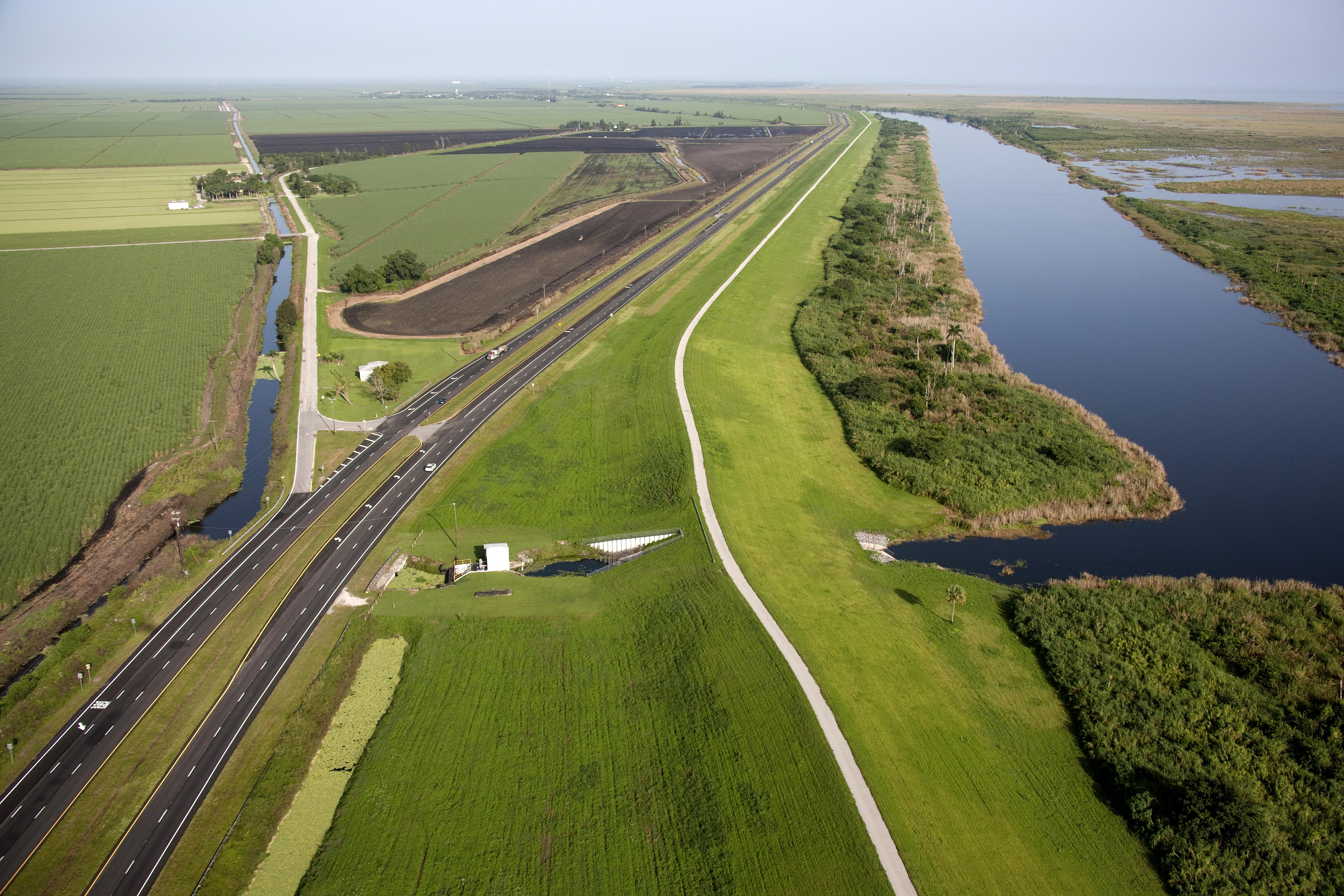 The Lake Okeechobee Scenic Trail, crown of the Herbert Hoover Dike, which surrounds Lake Okeechobee. This section is near South Bay at the southernmost end of the lake. (Photo by Mark Bias) Via Creative Commons, JaxStrong.